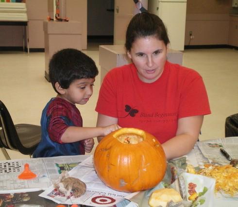 Shawn Marsolais decorates a Halloween pumpkin with Blind Beginnings children.