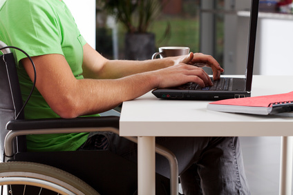 Young man on wheelchair writing on laptop and drinking coffee